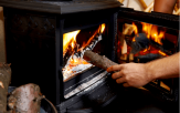 Adding wood to stove