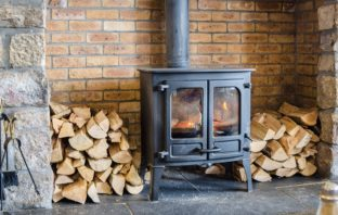 Tradional Wood Burning Stove in a Brick Fireplace. Two piles of firewood are placed at both sides of the stove and some fireplace accessories are visible at the left side of the photo.