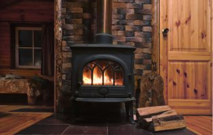 Wood burning stove with pile of logs