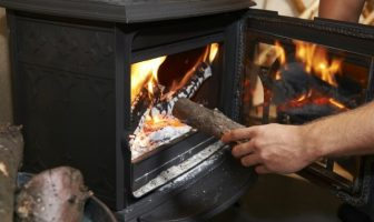 Person putting a log on a wood burning fire