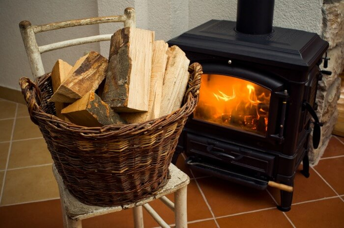 Basket of logs next to a wood burning stove