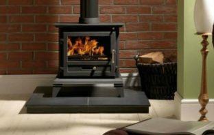 Log burner sitting on hearth against brick wall