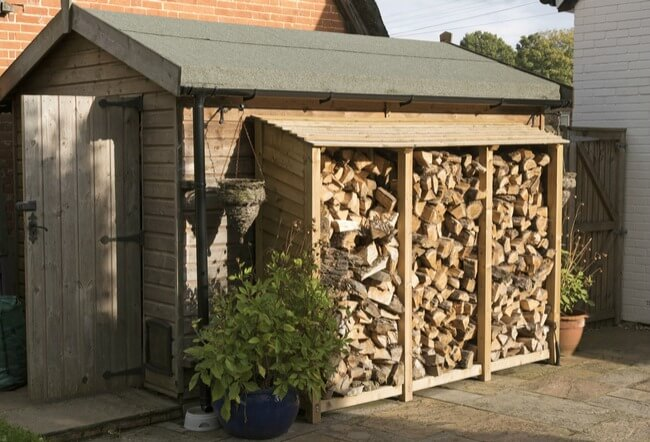 Log store in garden against shed