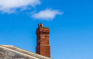 Brick chimney set against blue sky