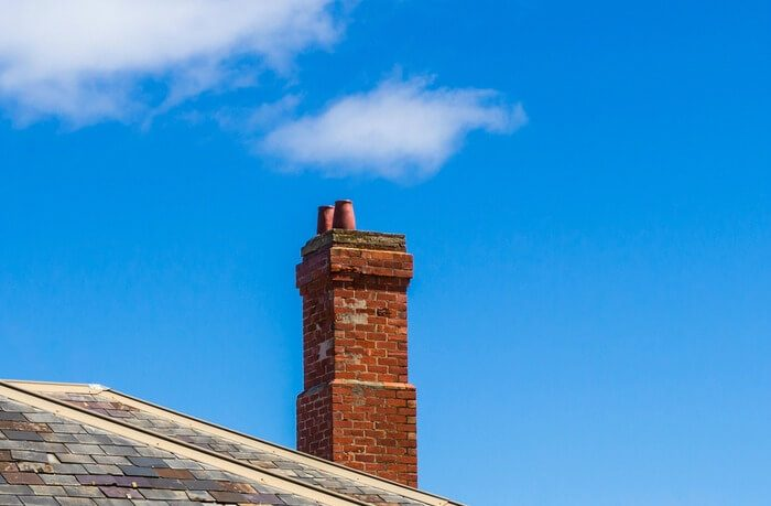 Brick chimney set against blue sky