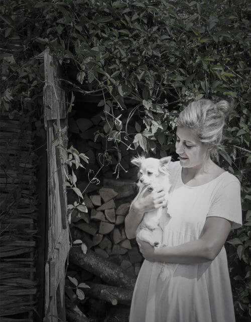 Jess holding her dog in her cotswolds home